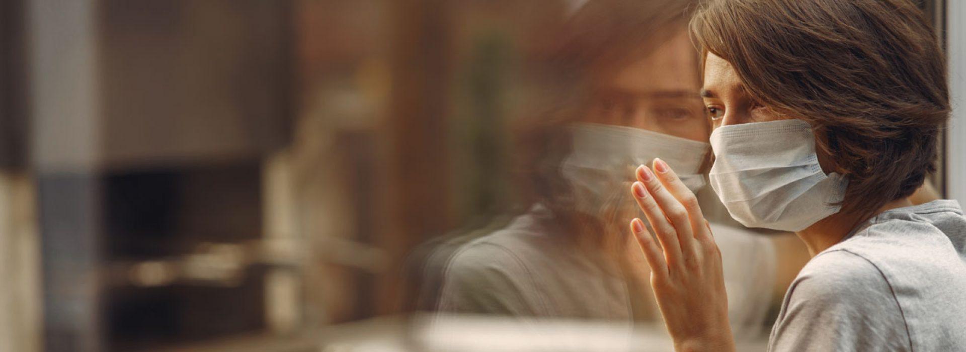 Woman in mask. Coronavirus theme. Lady by the window.